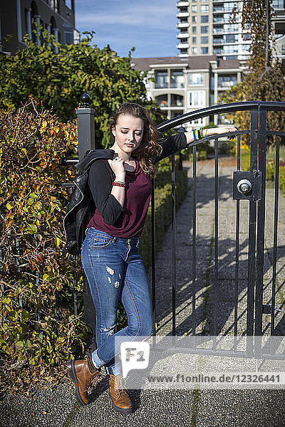 A young woman stands leaning against a metal gate holding a leather jacket and looking confident with housing in the background; New Westminster  British Columbia  Canada