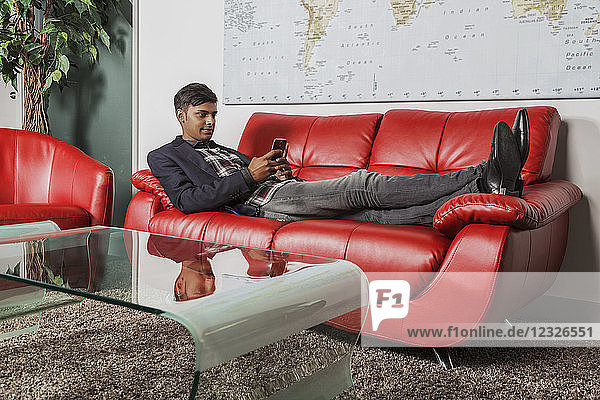 Young millennial businessman using his smart phone in the lobby of a workplace while laying on a couch; Sherwood Park  Alberta  Canada