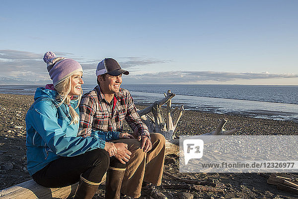 A young couple sits on a piece of driftwood on a beach looking out to the ocean at sunset; Anchorage  Alaska  United States of America