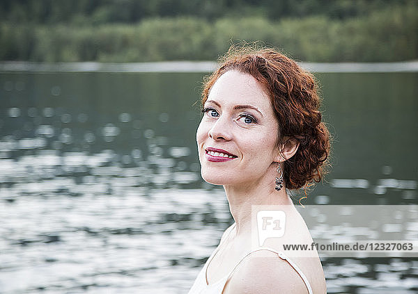 Portrait of a woman with red hair and a lake in the background; British Columbia  Canada