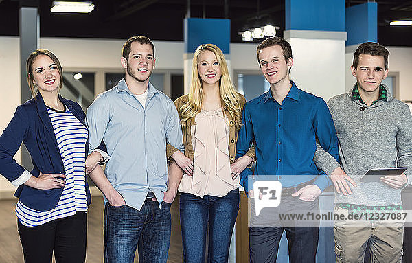 Portrait of a group of young millennial professionals standing together arm in arm in the workplace; Sherwood Park  Alberta  Canada