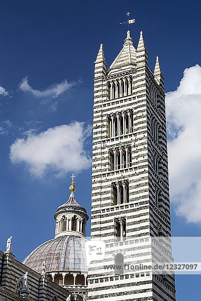 Tall striped tower of Siena Cathedral with dome  blue sky and clouds in the background; Siena  Tuscany  Italy