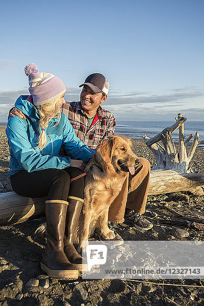 A young couple with their dog sit on a piece of driftwood on a beach at sunset; Anchorage  Alaska  United States of America