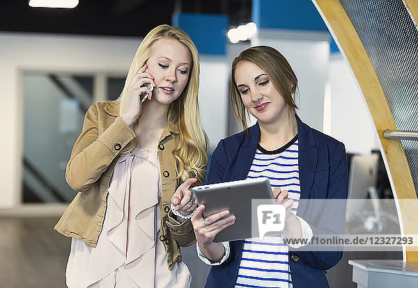 Two beautiful young millennial business women using technology in the workplace; Sherwood Park  Alberta  Canada