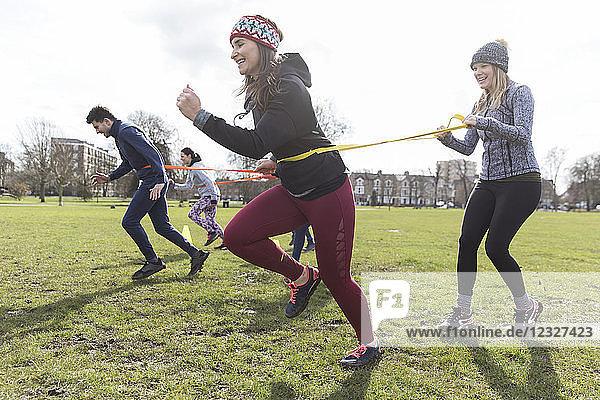 Women exercising  doing team building exercise in park