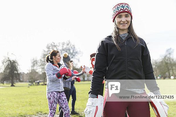 Portrait confident young woman boxing in park
