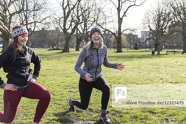 Smiling  confident women doing lunges in sunny park