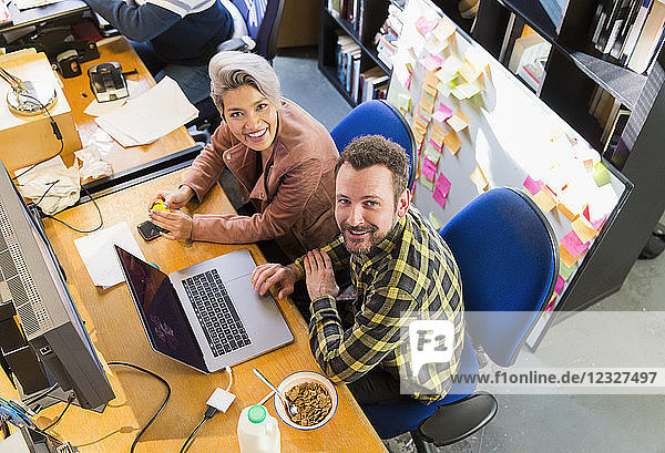 Portrait smiling  confident creative business people eating cereal  working at laptop in office