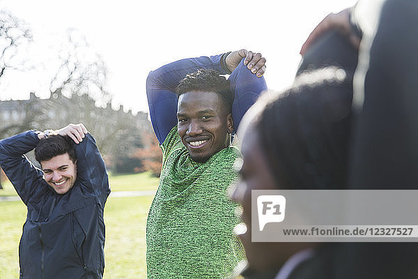 Portrait smiling  confident man stretching  exercising in park