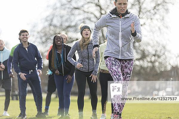 Team cheering woman running in sunny park