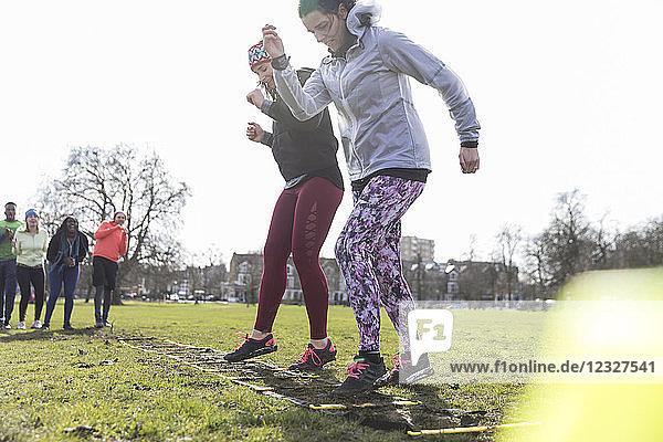 Women exercising  doing ladder drill in sunny park