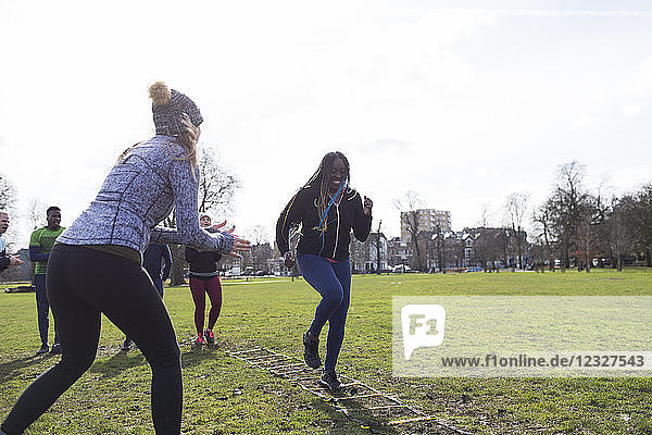 Woman cheering friend doing speed ladder drill in sunny park