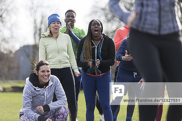 Team cheering woman exercising in park