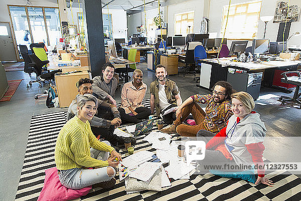 Portrait confident creative business team meeting  brainstorming in circle on office floor