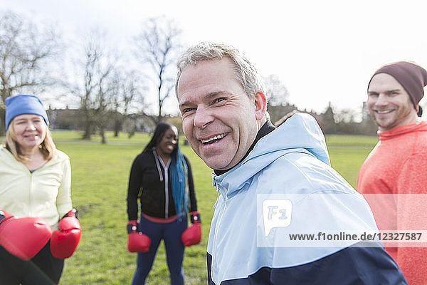 Portrait smiling  confident man boxing with friends in park