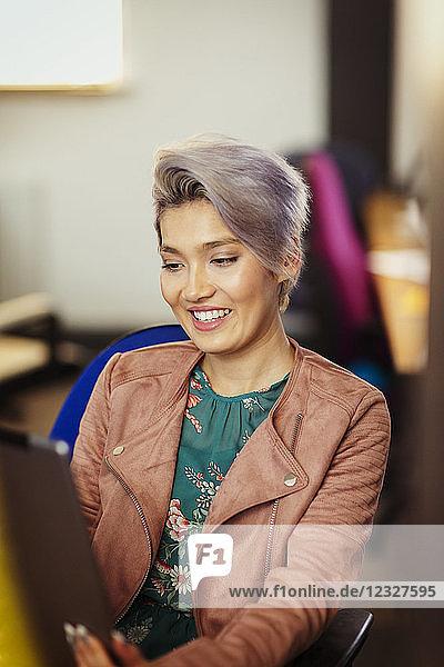 Smiling creative businesswoman using digital tablet