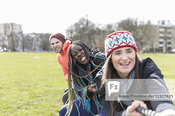 Determined team pulling rope in tug-of-war in park