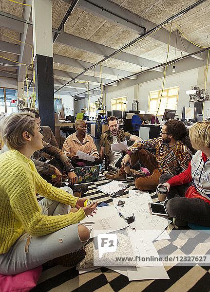 Creative business team meeting  brainstorming in circle on office floor