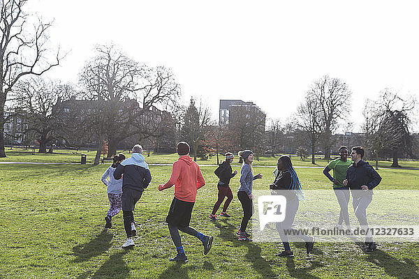 Runners jogging in circle in sunny park