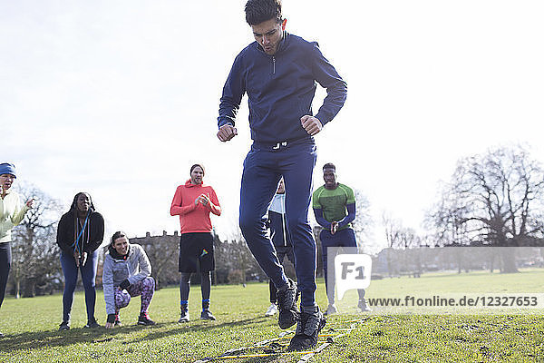 Focused man doing speed ladder drill in sunny park