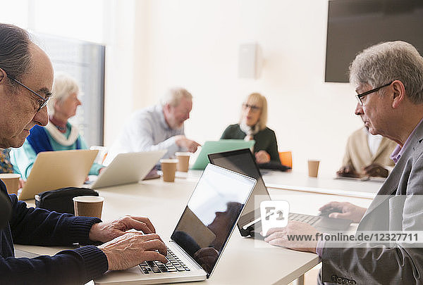 Senior businessmen using laptops in conference room meeting