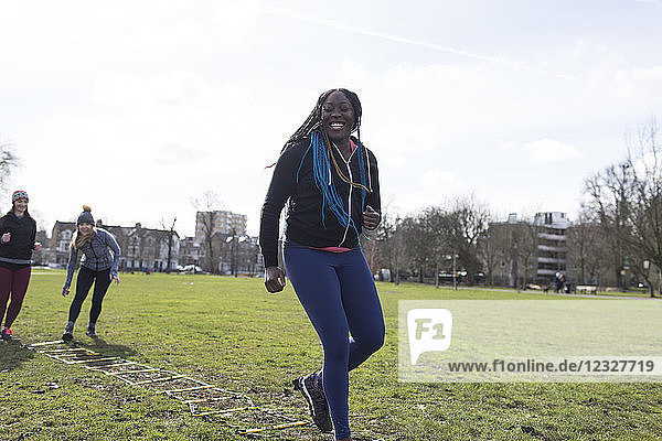 Smiling  confident woman doing speed ladder drill in sunny park
