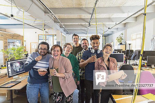 Portrait happy  playful creative business team in open plan office