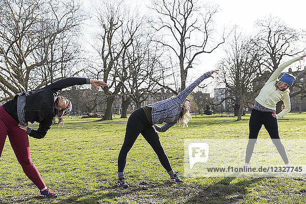 Women runners stretching in sunny park