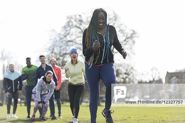 Team cheering woman running in park