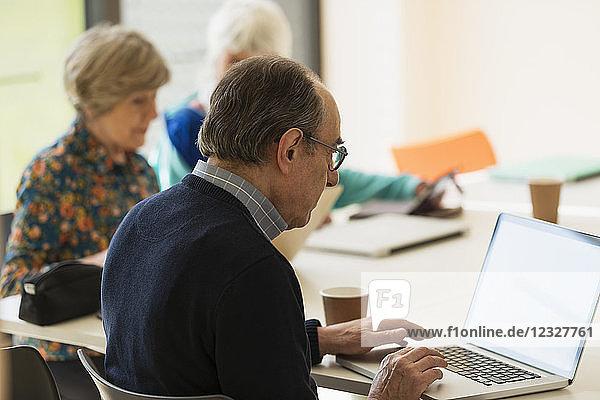 Senior businessman using laptop in meeting
