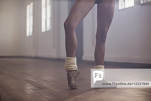 Young female ballet dancer stretching foot in dance studio
