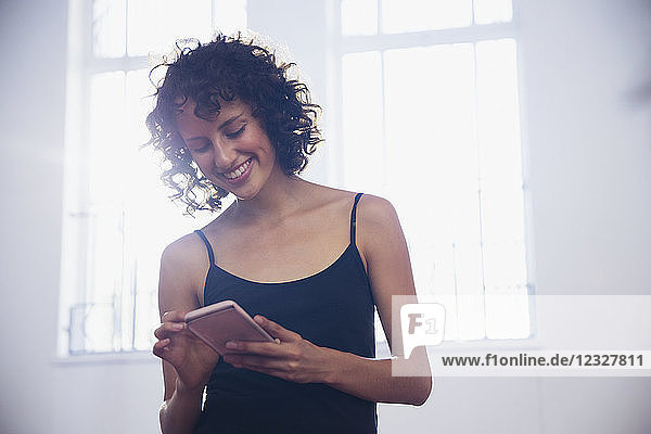 Smiling young female dancer texting with smart phone in dance studio