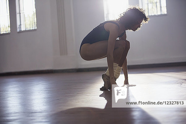 Strong young female dancer stretching toes in dance studio