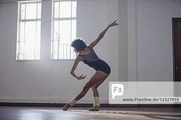 Graceful young female dancer practicing in dance studio