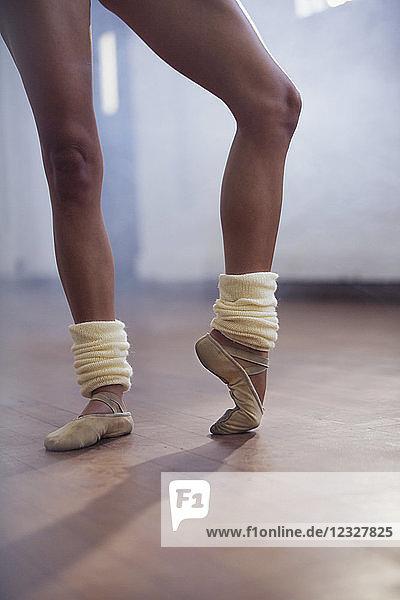 Ballet dancer stretching toes in dance studio