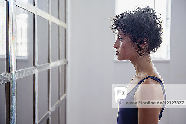 Profile serious young female dancer standing at mirror in dance studio