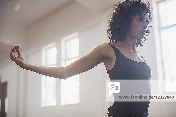 Focused  determined young female dancer stretching in dance studio