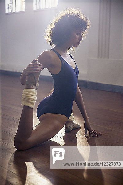 Strong young female dancer stretching leg in dance studio