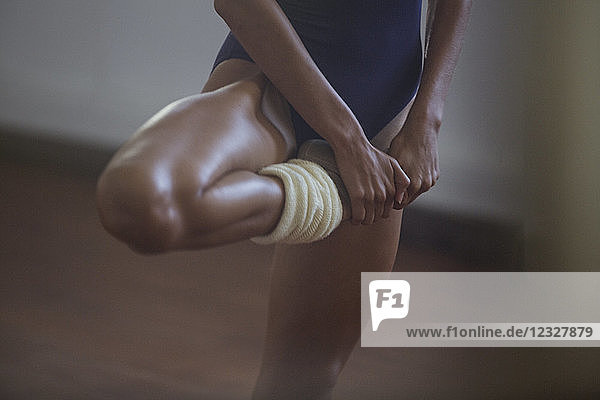 Strong  young female dancer stretching leg