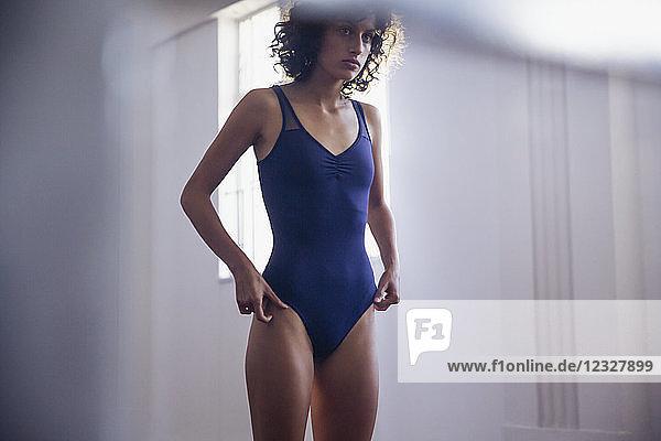 Young female dancer standing at mirror in dance studio