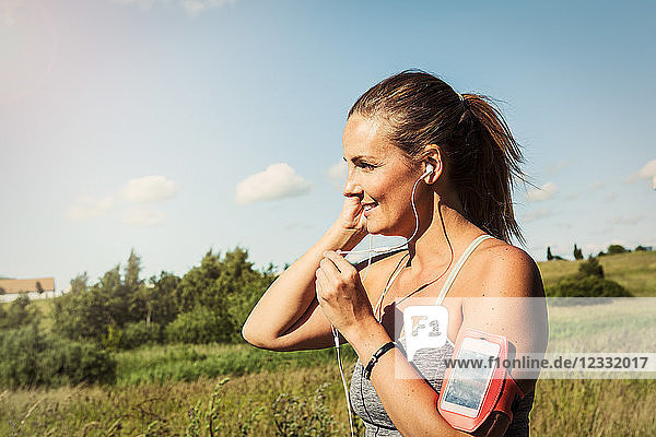 Woman listening music through mobile phone on arm band while exercising against sky