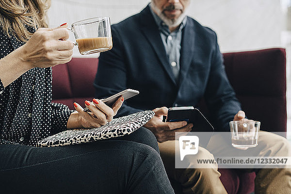 Midsection of business people using mobile phones and having tea on couch during conference