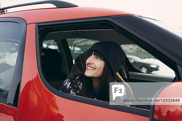 Smiling woman looking away while sitting in red car