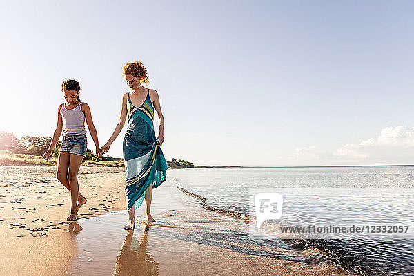 Full length of woman holding hands with daughter while walking on shore at beach against sky