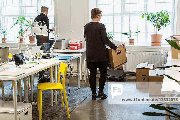 Rear view of businesswoman carrying cardboard box by desk in creative office
