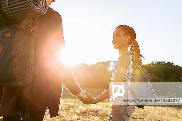 Smiling girl holding hands with mother while hiking at park against sky during sunset