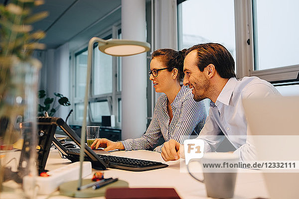 Smiling colleagues using laptop while sitting at desk in creative office