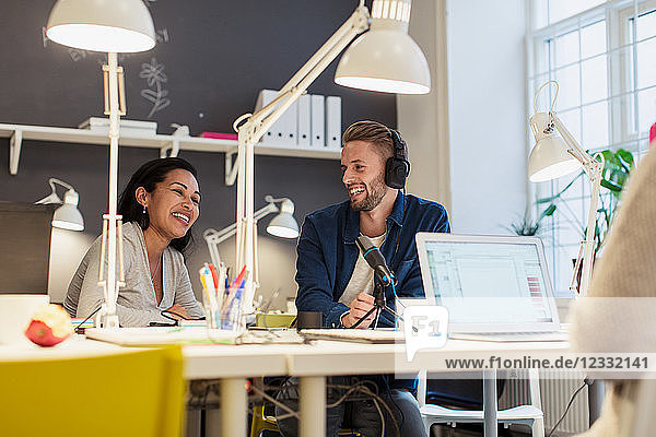 Cheerful multi-ethnic business colleagues sitting at desk with laptop and microphone in creative office