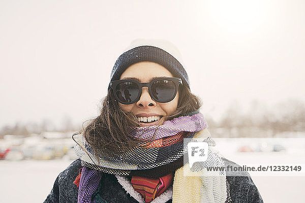 Close-up of smiling woman wearing scarf and sunglasses at park during winter