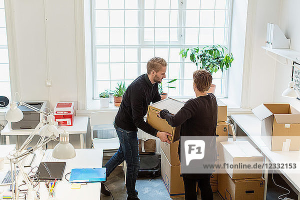 High angle view of business colleagues stacking cardboard boxes by window in creative office